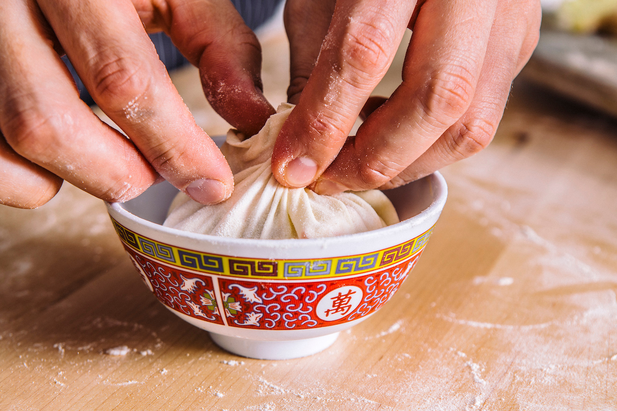 Hands wrapping up a dumpling