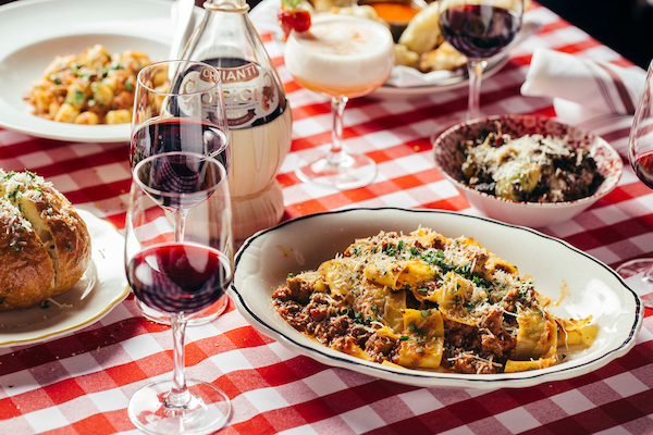 Pappardelle pasta surrounded by glasses of red wine