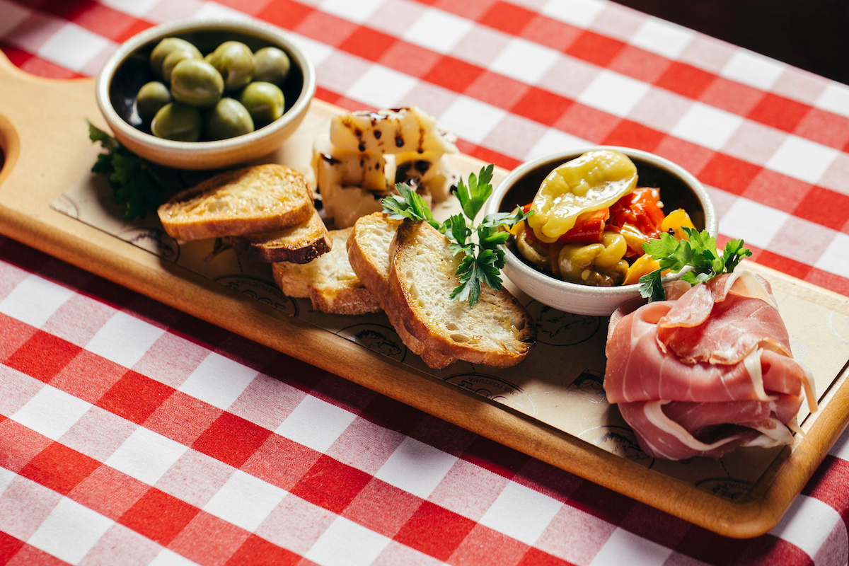 An antipasti platter with meats, cheeses, and olives.