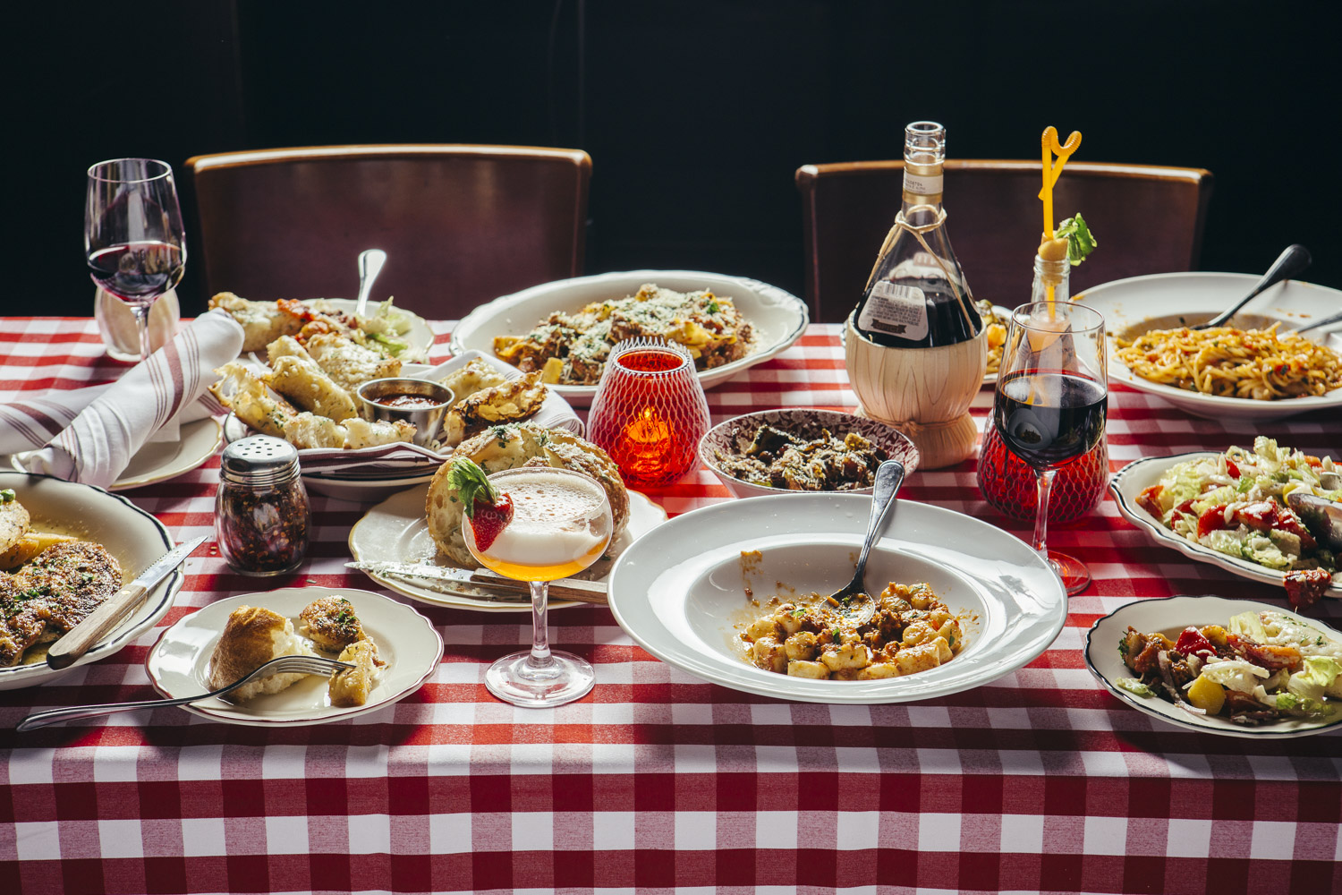 A spread of Italian dishes on a red-checkered tablecloth