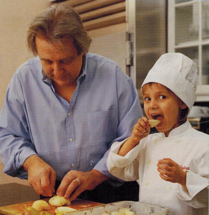 An old photo of Jean Joho and his daughter cooking in the kitchen
