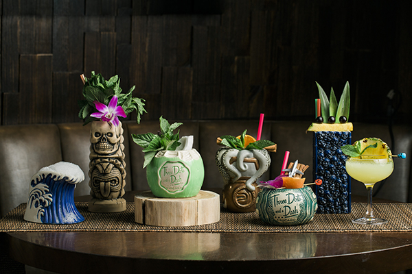 Tiki cocktails lined up on a table of Three Dots and a Dash