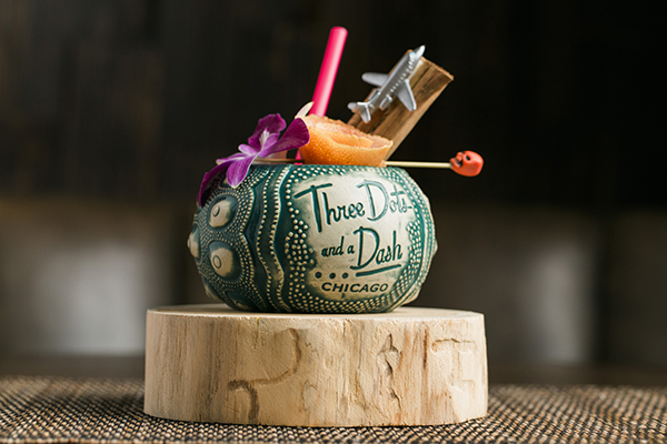 A tiki mug and cocktail on a wooden pedestal