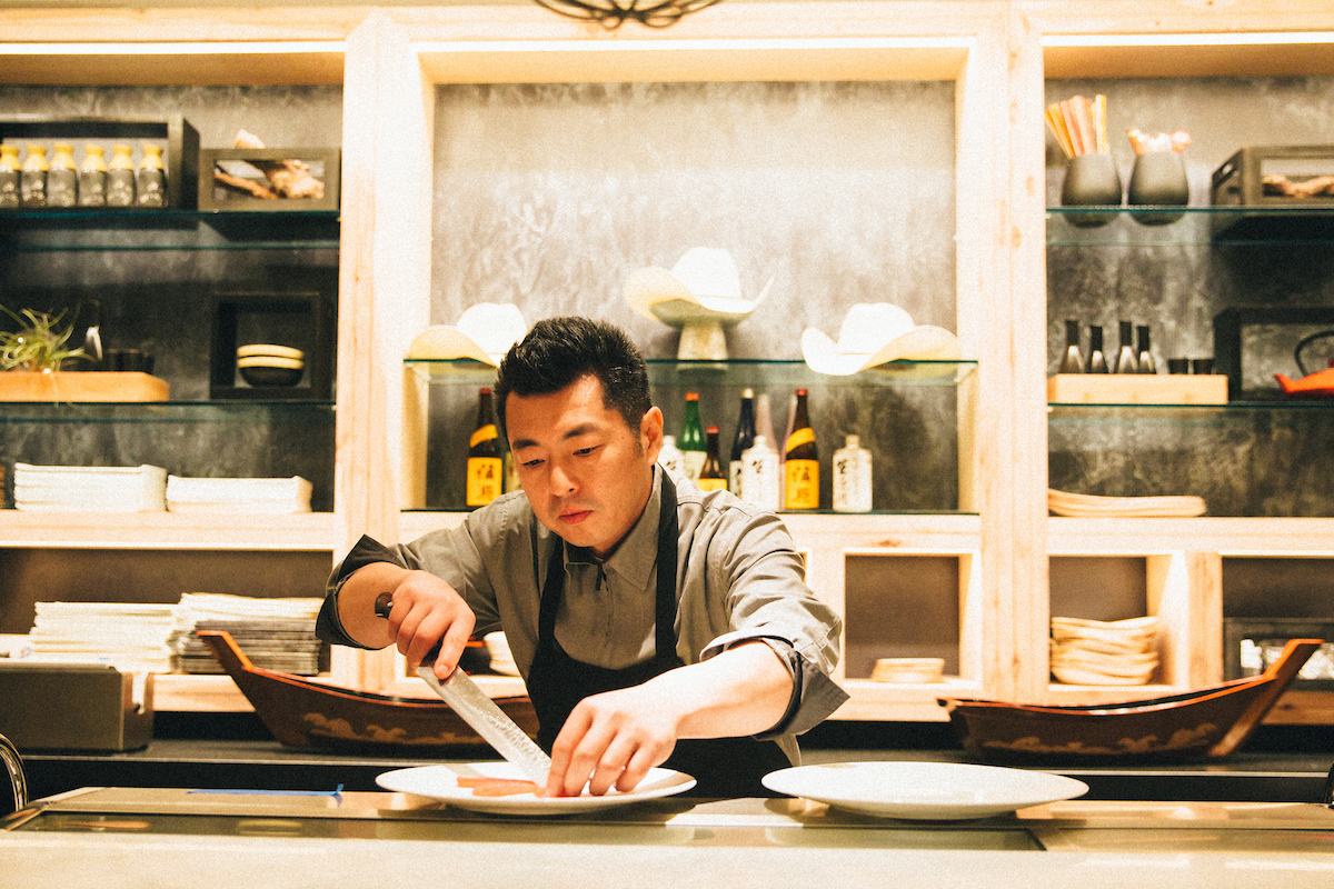 Chef Naoki reaching over the counter to slice a piece of fish on a plate