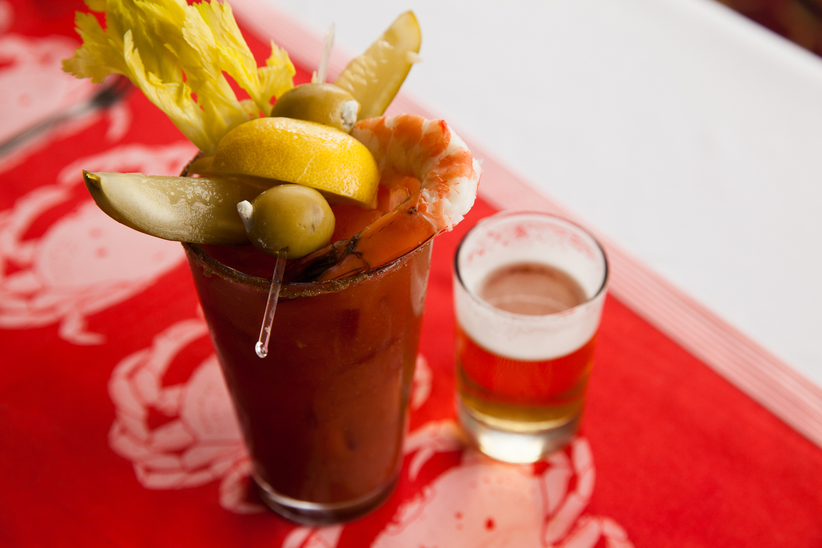 A bloody mary with all the toppings and a small glass of beer next to it