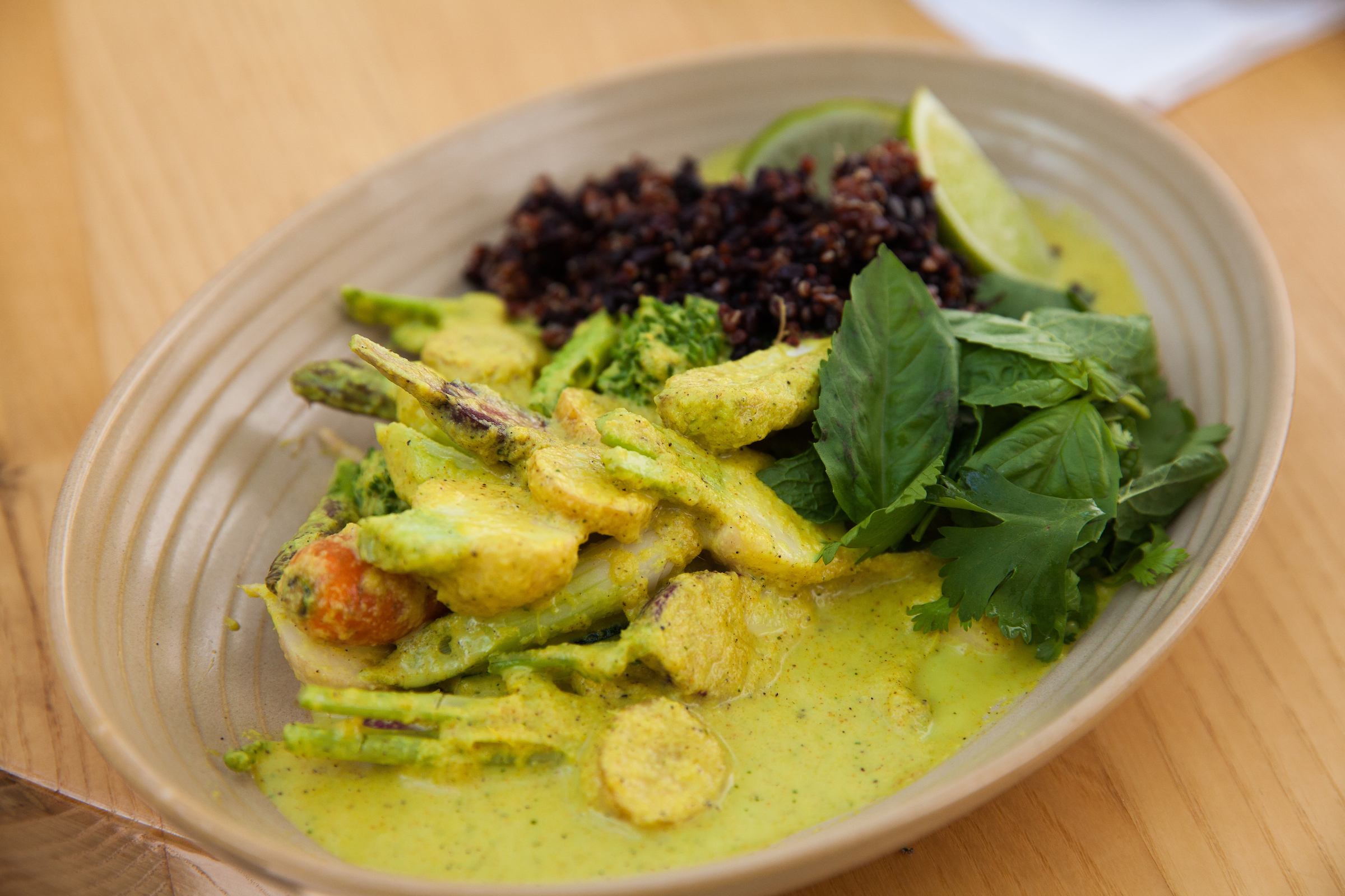 Vegetables in a green curry sauce with herbs lime wedges and black quinoa