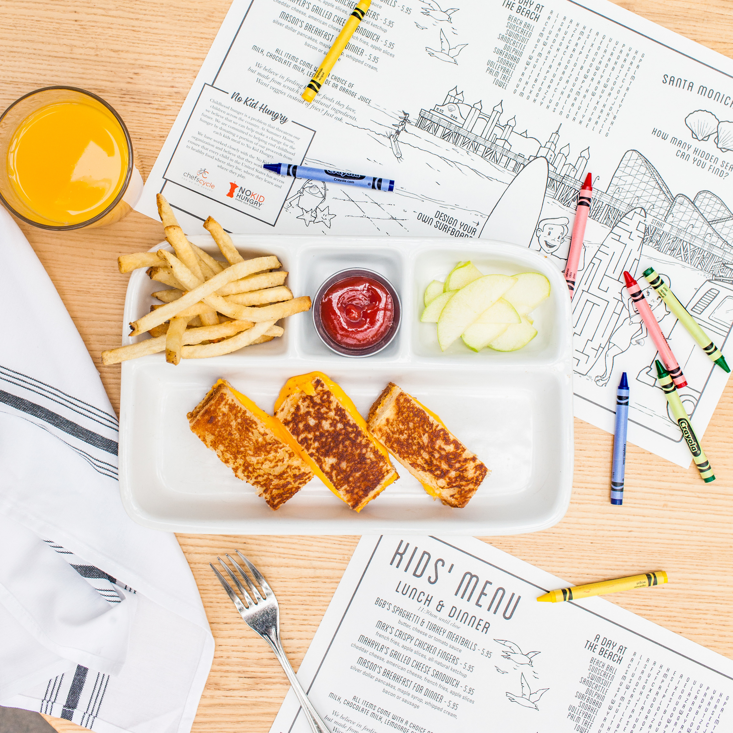 An overhead shot of the grilled cheese kid's meal at Summer House with the kids menus below it and crayons scattered about