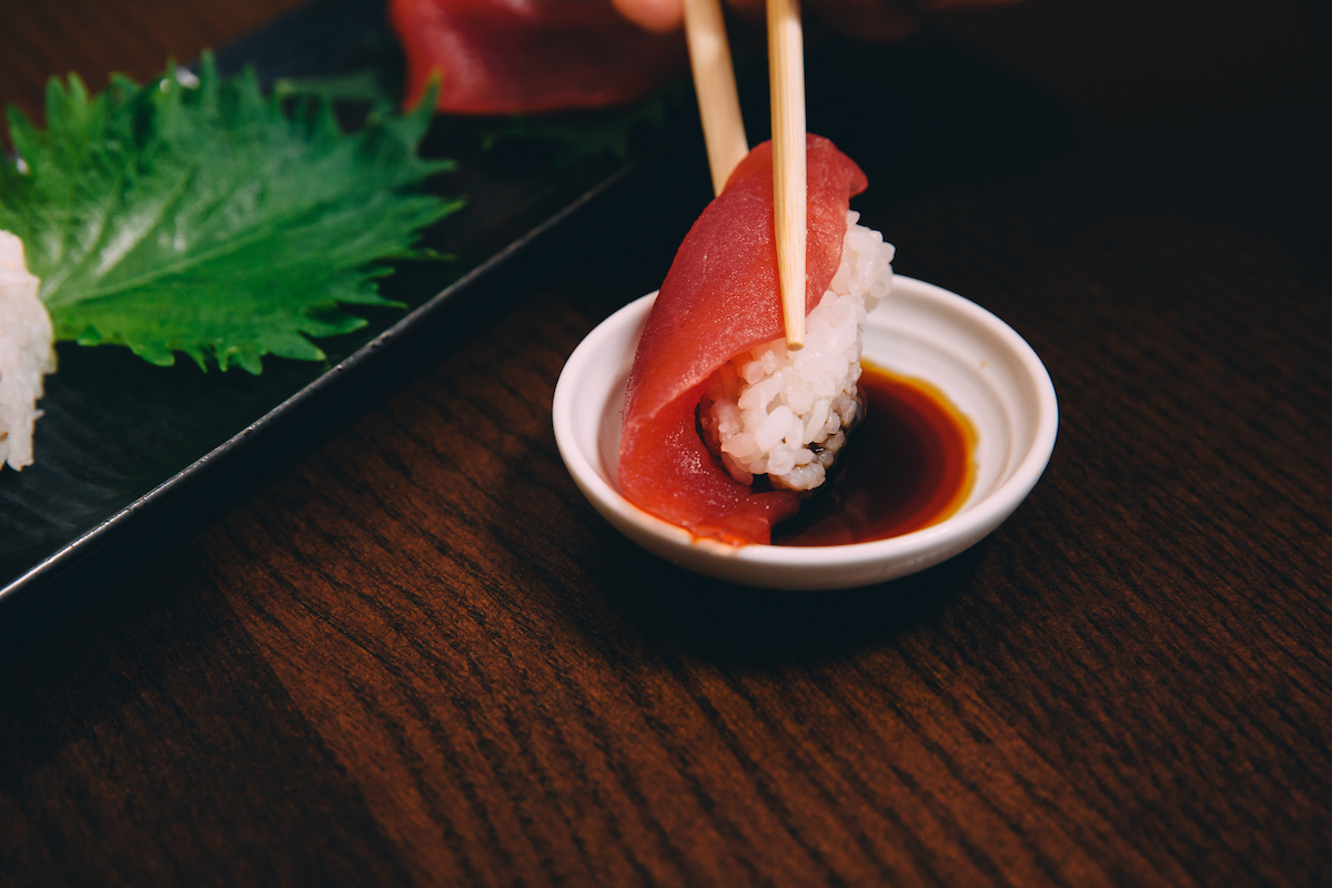 Tuna Nigir being dipped in soy sauce
