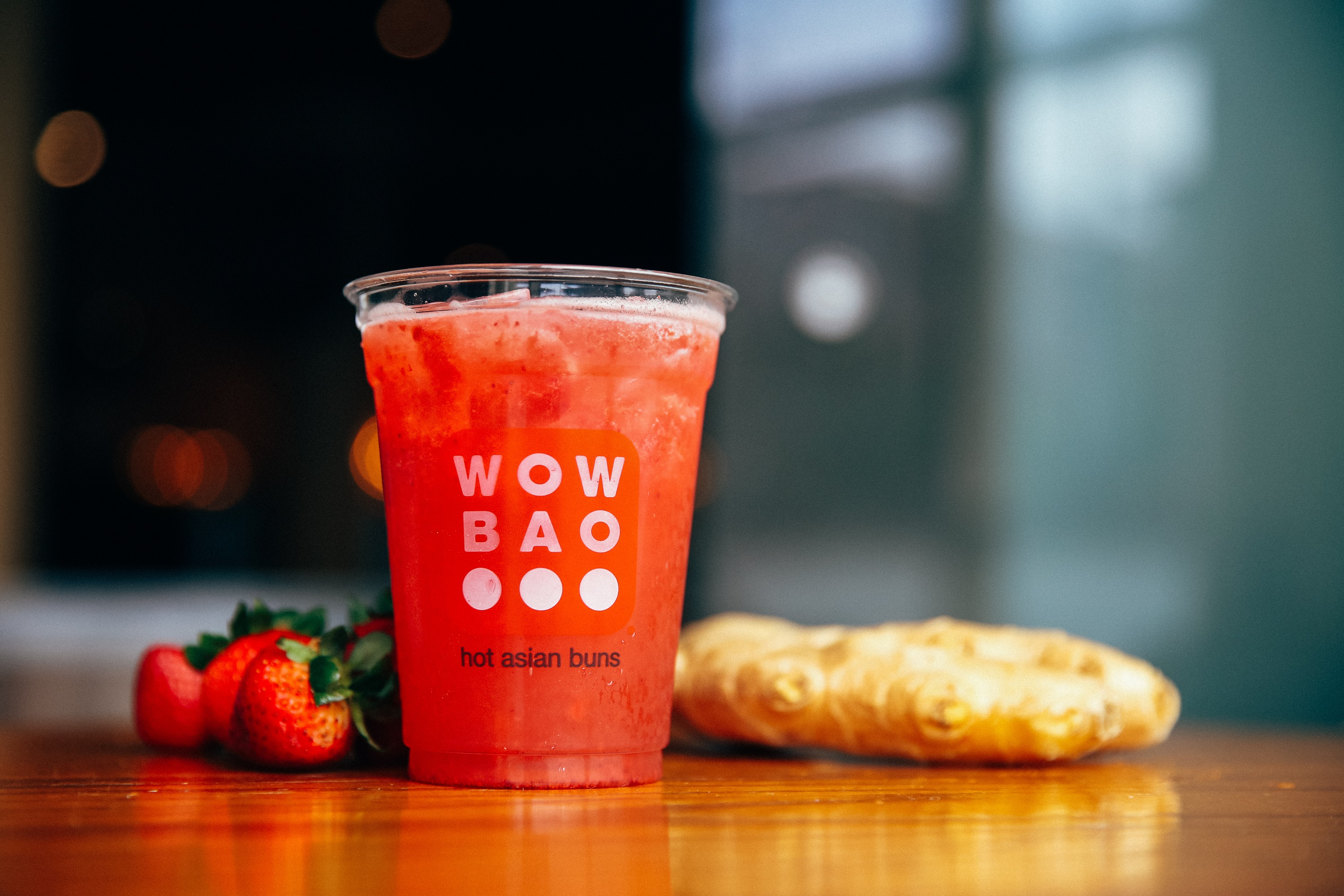 A plastic Wow Bao cup that is filled with a red strawberry drink