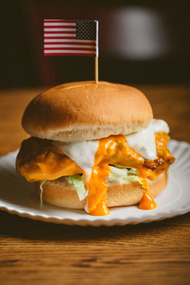 A buffalo chicken sandwich with the sauce dripping down the sides of the bun