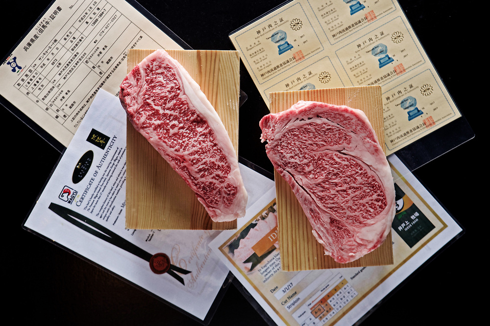 raw wagyu steaks on wooden blocks with awards