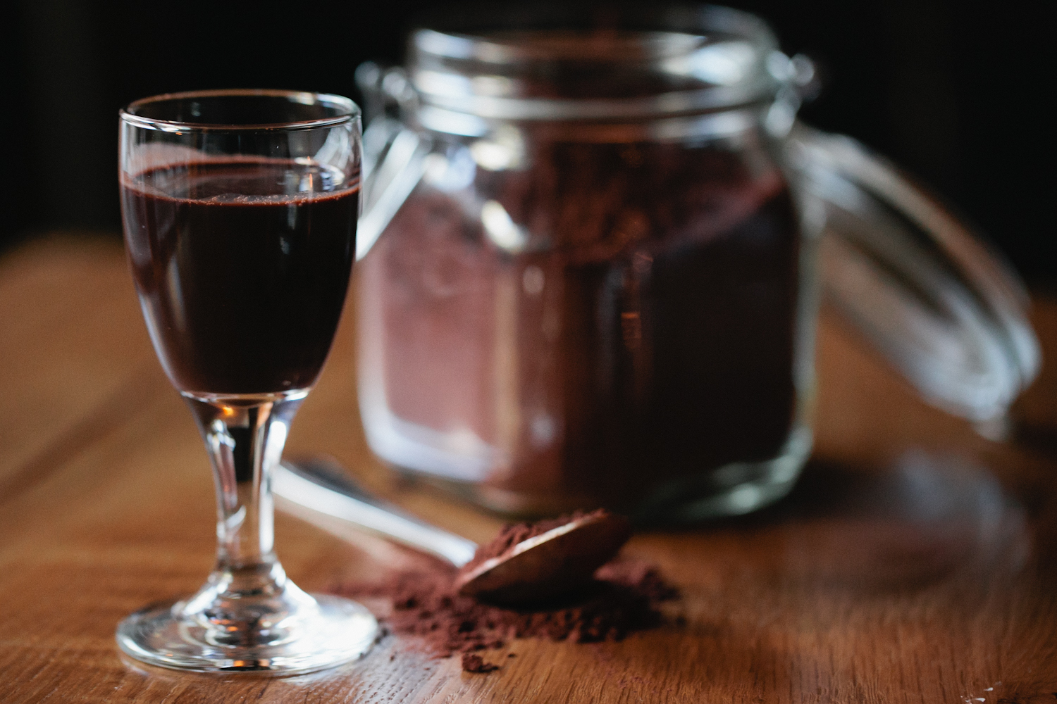 Osteria via Stato's Chocolacello in a glass with a bowl of fresh cocoa powder behind it