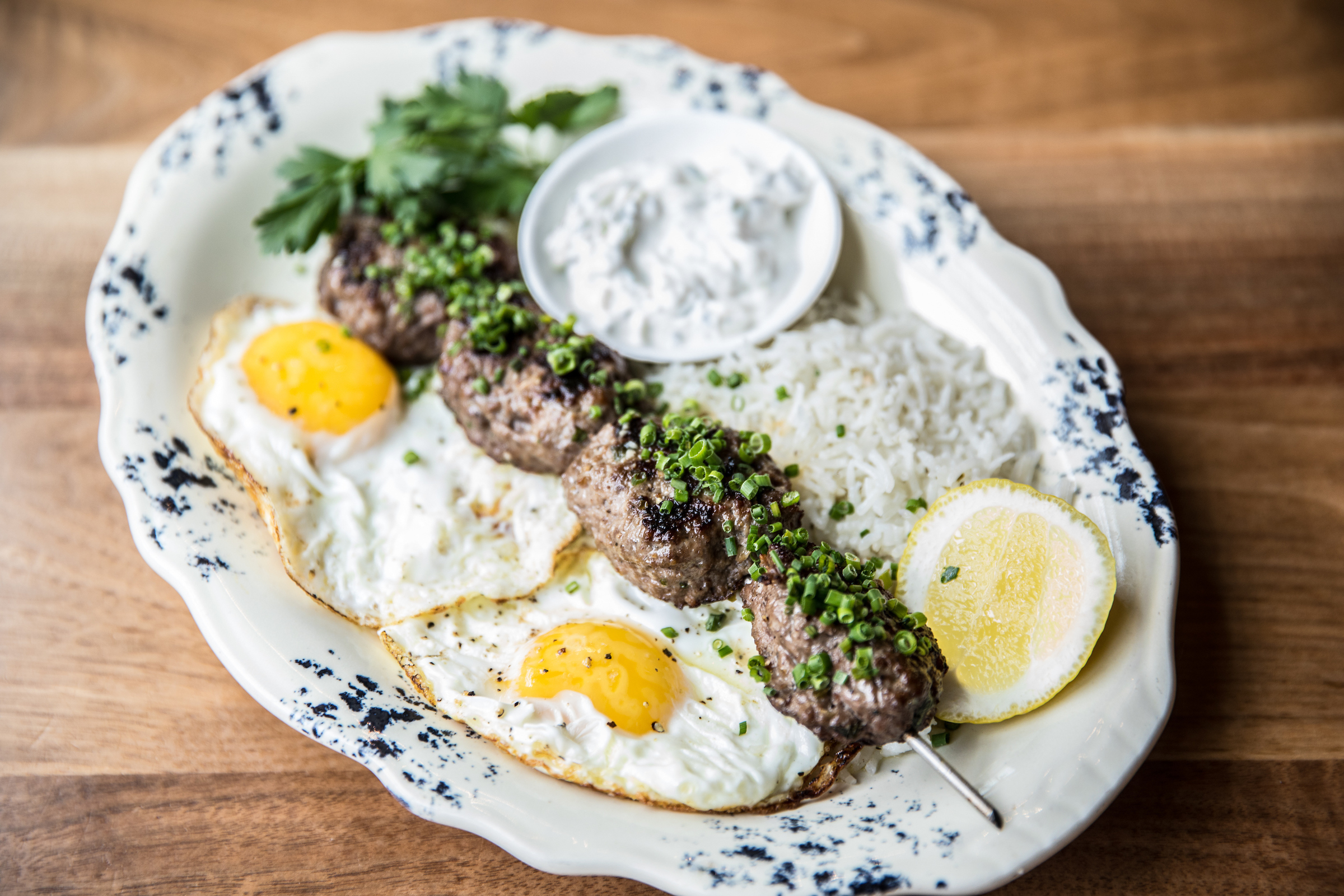 On a beautiful middle-eastern colored platter sits 2 egg with kefta, rice, and tzatiki