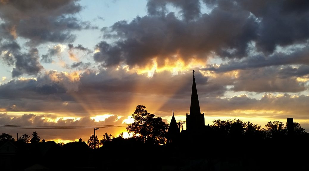 photo showing crepuscular ray at sunset in a panorama over a sillouhette of a church steeple