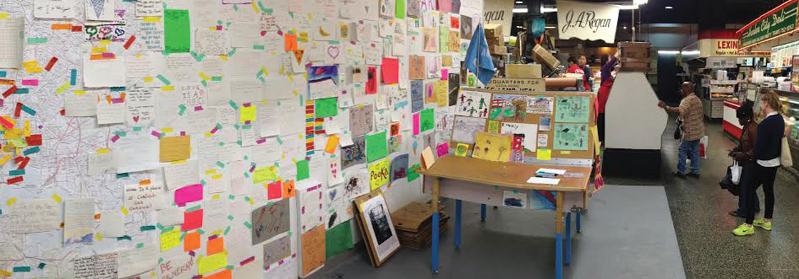A table covered with art making supplies sits next to a wall filled with art in an indoor marketplace.