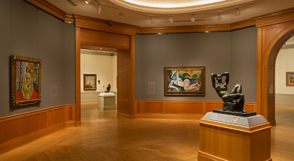 An image of the Cone wing, with many colorful Matisse's adorning the gallery 		walls.