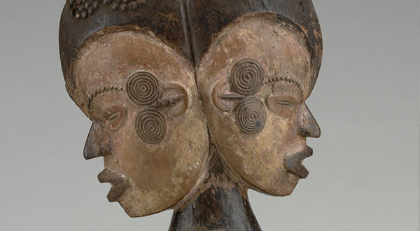 A headdress topped with two heads facing away from each other.