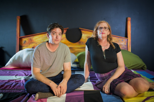 Two people sit next to each other on a bed. They face the viewer.
