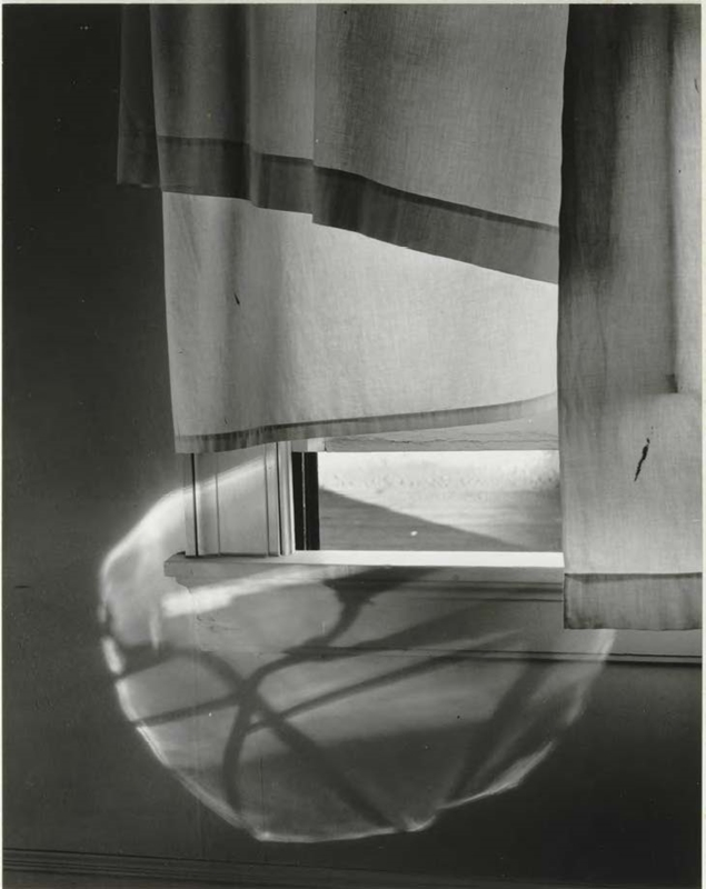 Black and white photo of a window with short curtains.