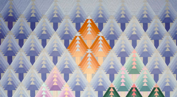 A field of triangles, many of them purple, fill the frame of this art quilt.