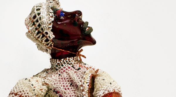 A beaded and glass sculpture of a woman.