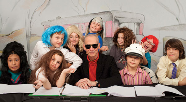 A group of children in costume sit at a table surrounding John Waters.