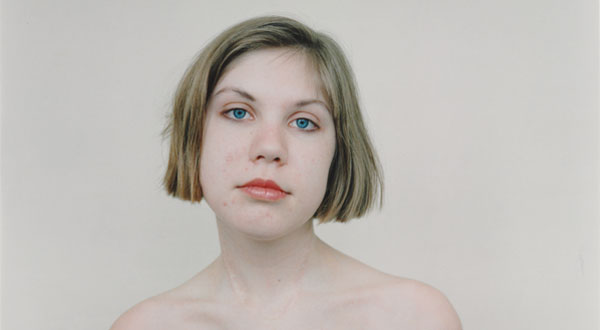 Photograph of a girl with bare shoulders, set against a plain background.