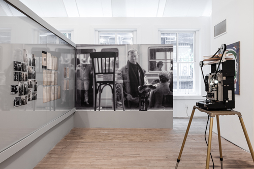 "in Pictures for 'Living with Pop. A Reproduction of Capitalist Realism' at Artists Space. Image for Installation view of the section ""Kaiserstraße 31A (1963)"" from Living with Pop. A Reproduction of Capitalist Realism, Artists Space, 2014. Center: Sigmar Polke in front of the window at Kaiserstraße 31A May 1963. Courtesy Archiv Kuttner, Erkrath. Photo: Undetermined photographer. Inkjet print on vinyl mounted to wall. Photo by Daniel Pérez."