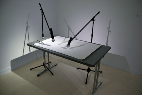 in Pictures for 'Beyond the Supersquare' at The Bronx Museum of the Arts. Image for Felipe Dulzaides, Interrogating Architecture, 2012, Desk, microphones with stands, and drawing, Dimensions variable. Courtesy of the artist.