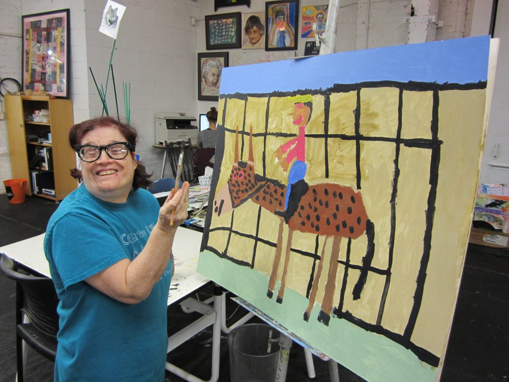 Woman holding a paintbrush in front of a large painting of a horseback rider and horse