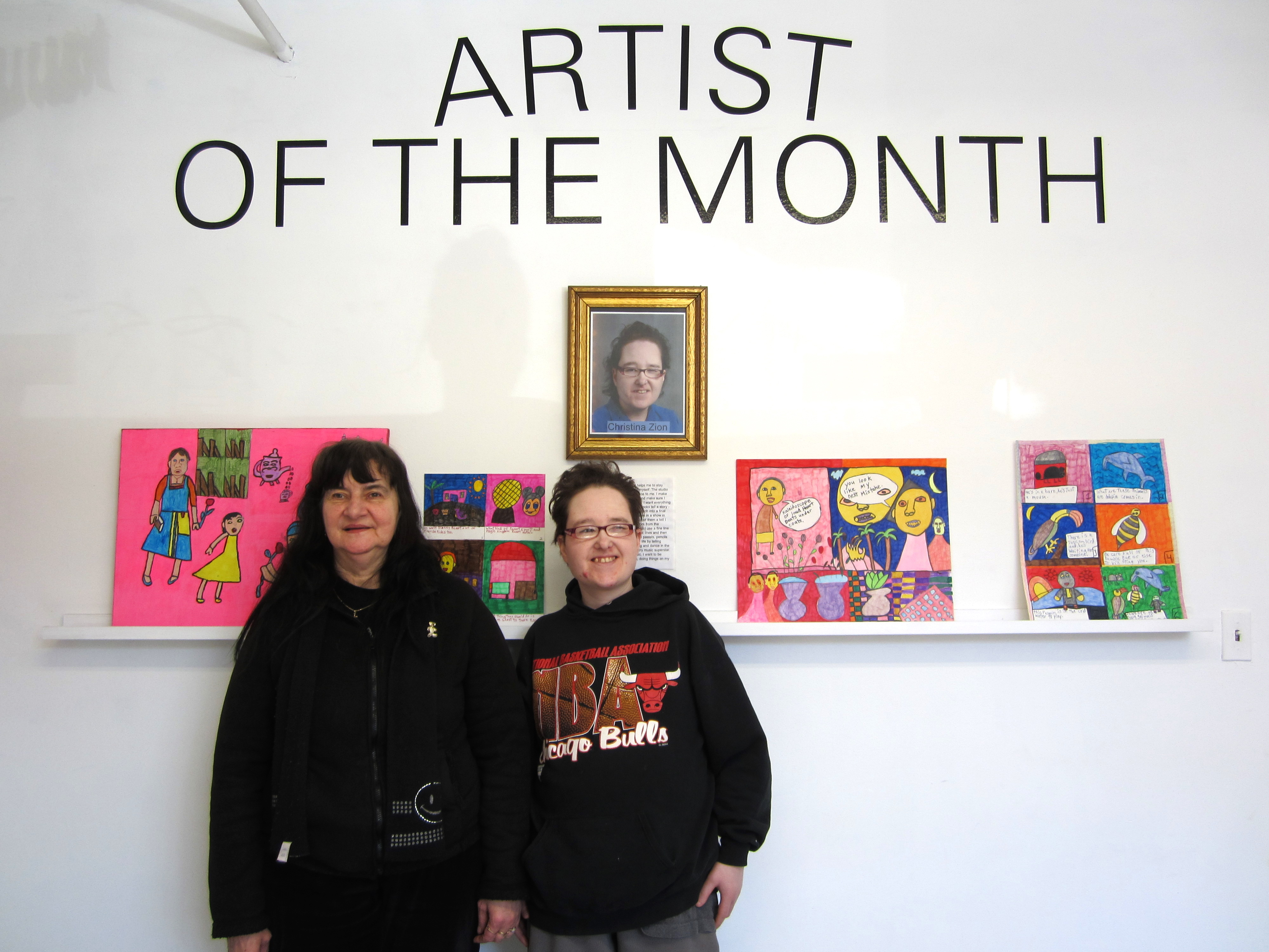 Two Women standing in front of a wall with four drawings