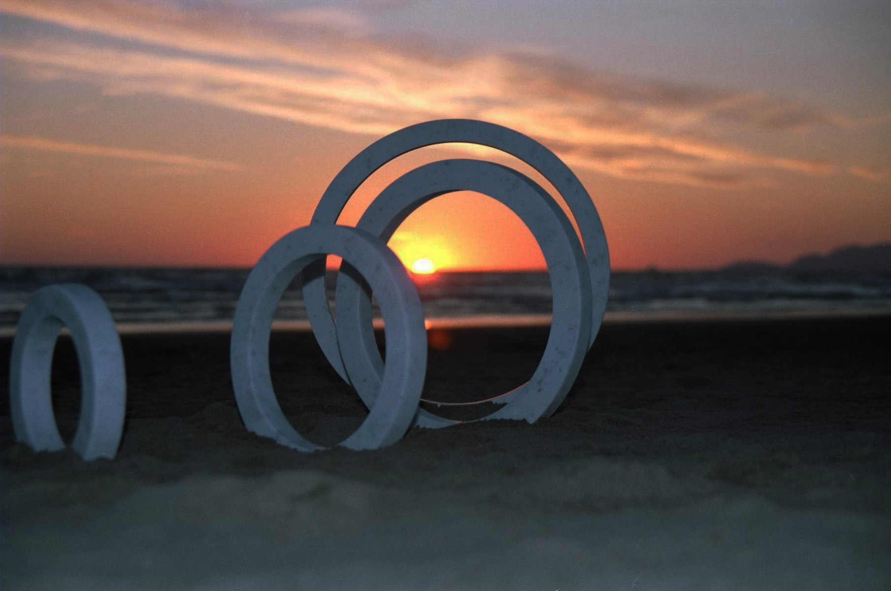 Four marble sculpture rings on the beach