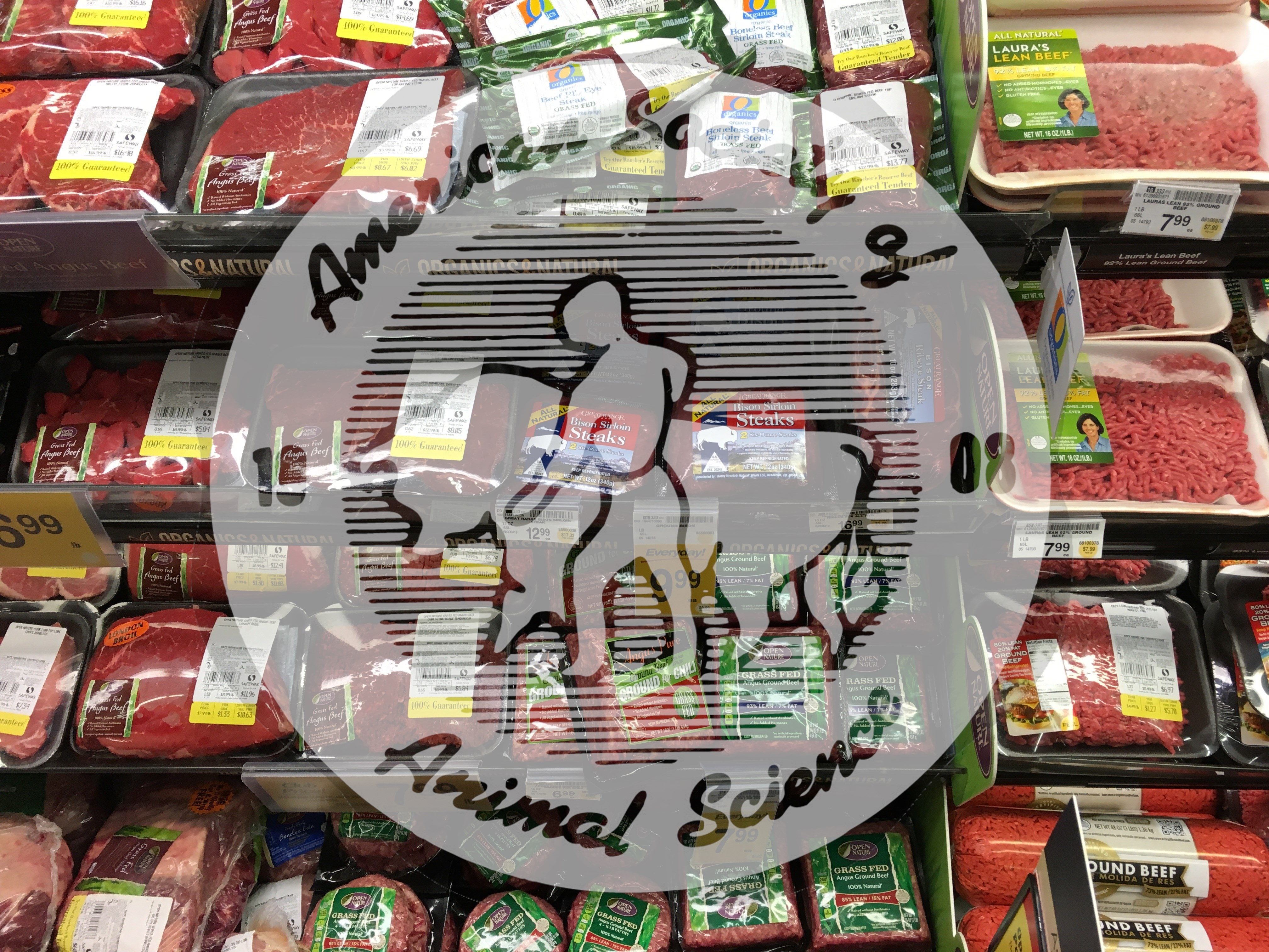 A meat case in a grocery store featuring different beef meat products.  Some of these products include commodity beef and branded beef products.  Branded beef products are different than commodity beef in either how the beef was raised or beef meets certain specifications for nutrient content or quality.  This meat case features organic, grass-fed and lean branded beef products.