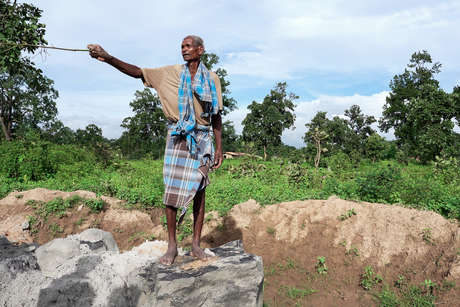 """An Adivasi man surveys the destruction of his ancestral land at the edge of what will become the Parsa mine, Hariharpur village. """"The workers come at night to do their work. If they are not thieves then what are they?"""""""