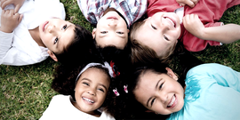 diverse laughing children on the ground together
