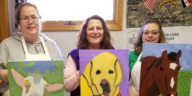 Four Women hold paintings of their pets they just made.