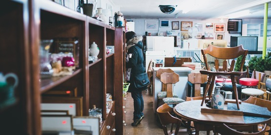 a woman looks through a thrift shop
