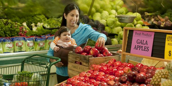 A woman and her infant shop for fruit at a grocery store.