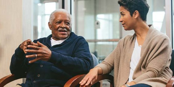 Older adult man sitting with a younger woman.