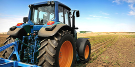 A blue tractor working in a field