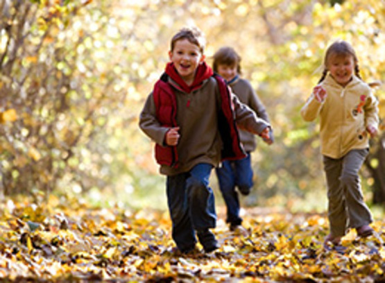 children running down a path in the forest