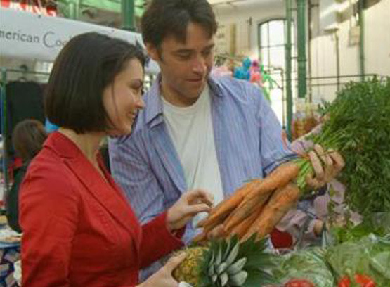 couple inspecting carrots at a grocery store or farmers market