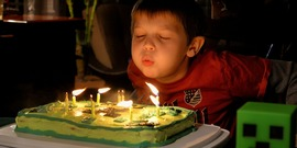 A boy blowing out his birthday candles