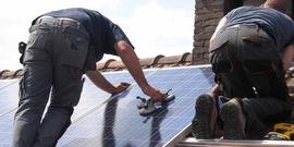2 men on a roof installing a solar panel
