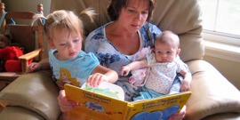 Young girl and infant sit on a care provider's lap while reading a book