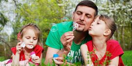 Father blowing bubbles with kids laying in the grass