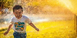 a child runs through a sprinkler