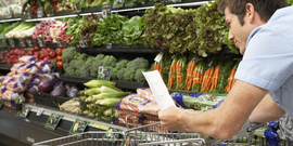 man checking list while grocery shopping