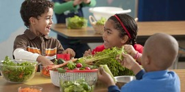 Children at a table with fresh vegetables