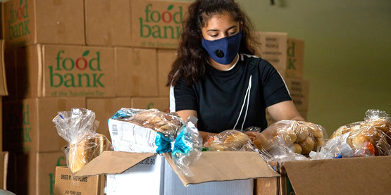 High school student sorts breads for distribution by Tompkins County Food Task Force in July 2020.